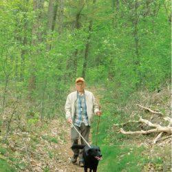 Han wandelt met zijn hond in het bos